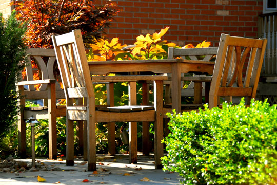 wooden patio furniture with fall foliage backdrop
